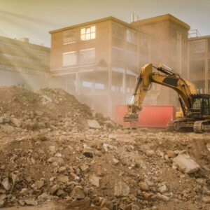 Excavator on construction site with stone rubbish in back lit
